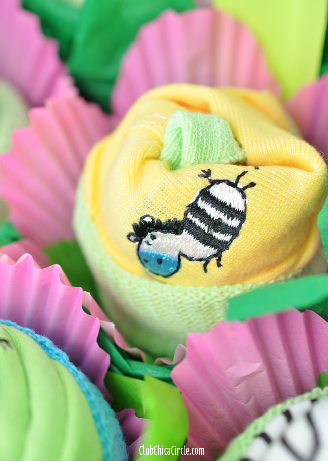 Baby onesie rolled into flowers for baby shower